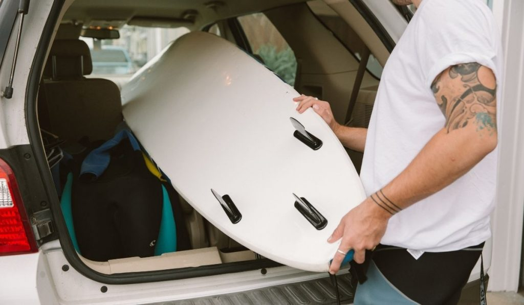 Man loading surfboard into car