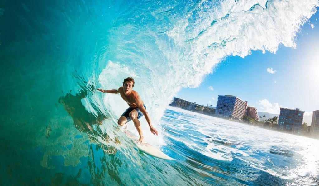 Man surfing a wave with buildings in the background