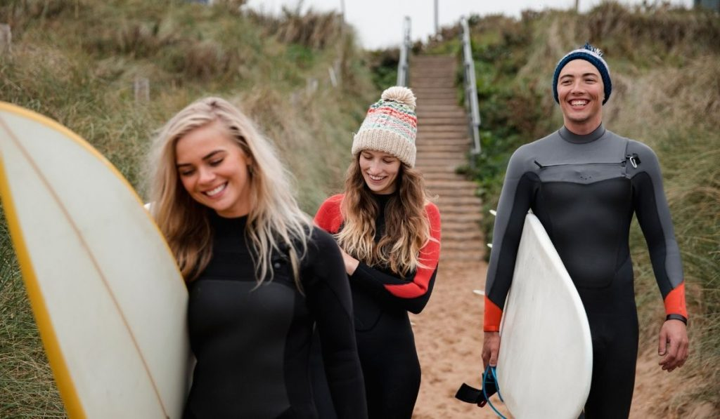 Three smiling surfers carrying their surf boards