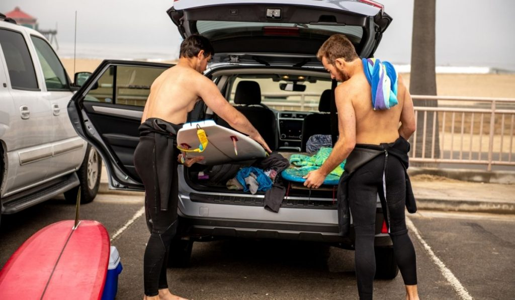 Two Surfers Unloading Surfboards From Car