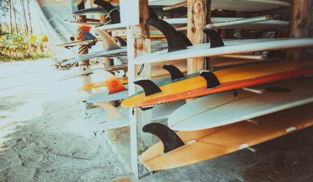 a rack of surf boards with various fins