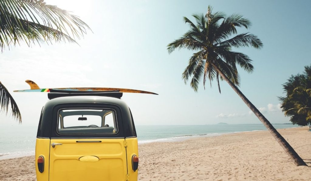 a yellow car at the beach with a surf board on it