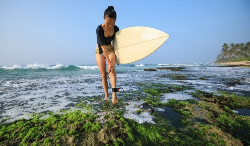 asian woman holding surfboard with knee injury
