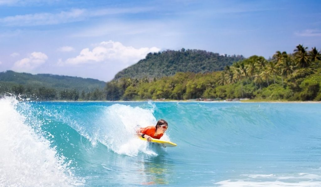 boy with orange shirt surfing a wave lying down on a surf board