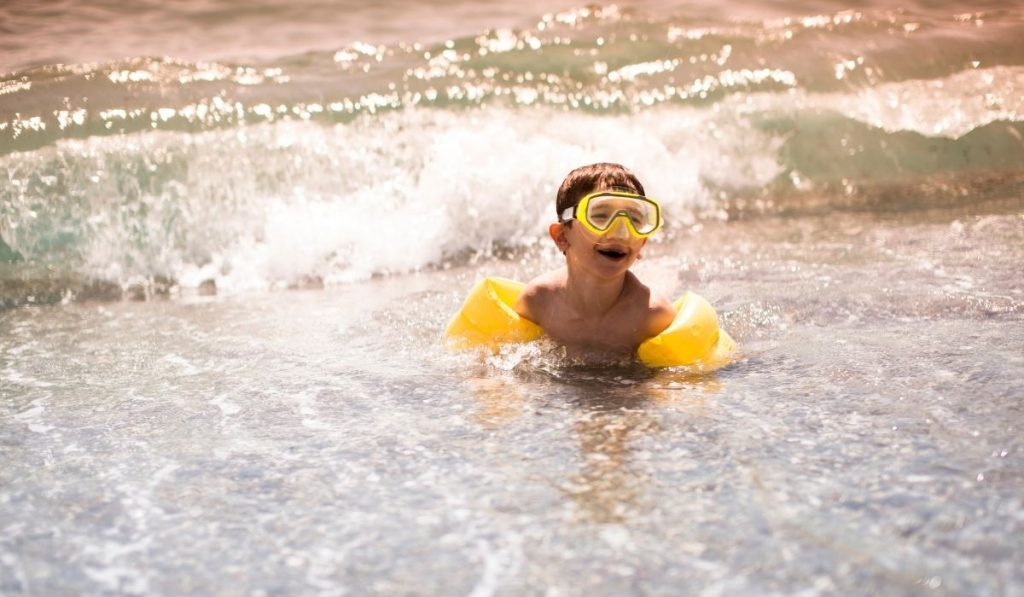 child in yellow arm floaters and goggles at the beach