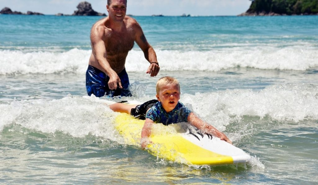 dad with child on a yellow and white surf board