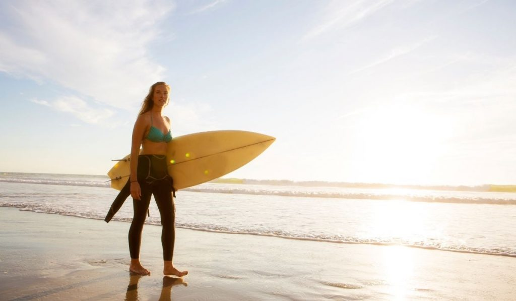 female surfer holding a surfboard walking by the shore