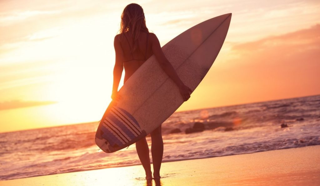 female surfer looking at the sunset holding her surfboard