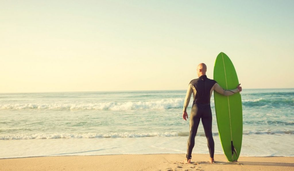 male surfer holding a surfboard at the shore