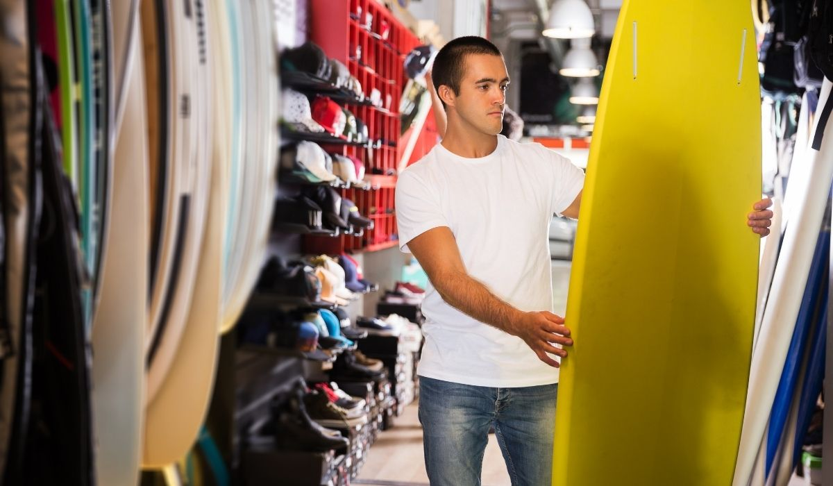 man buying a yellow surfboard