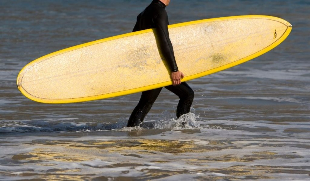man carrying a yellow longboard surfboard at the beach
