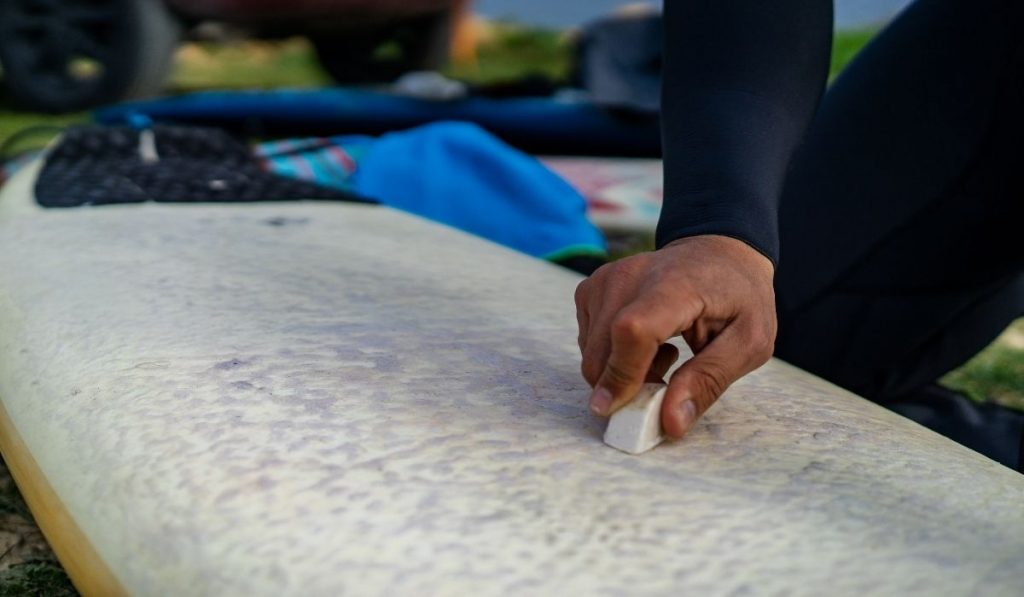 man cleaning the surfboard