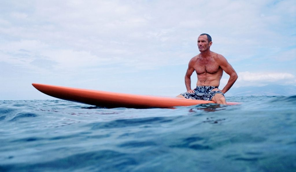 man sitting on an orange surf board in the water