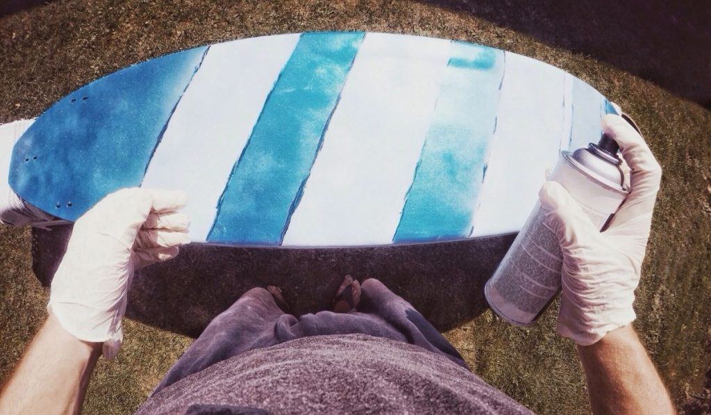 person spray painting a surf board in blue and white stripe design