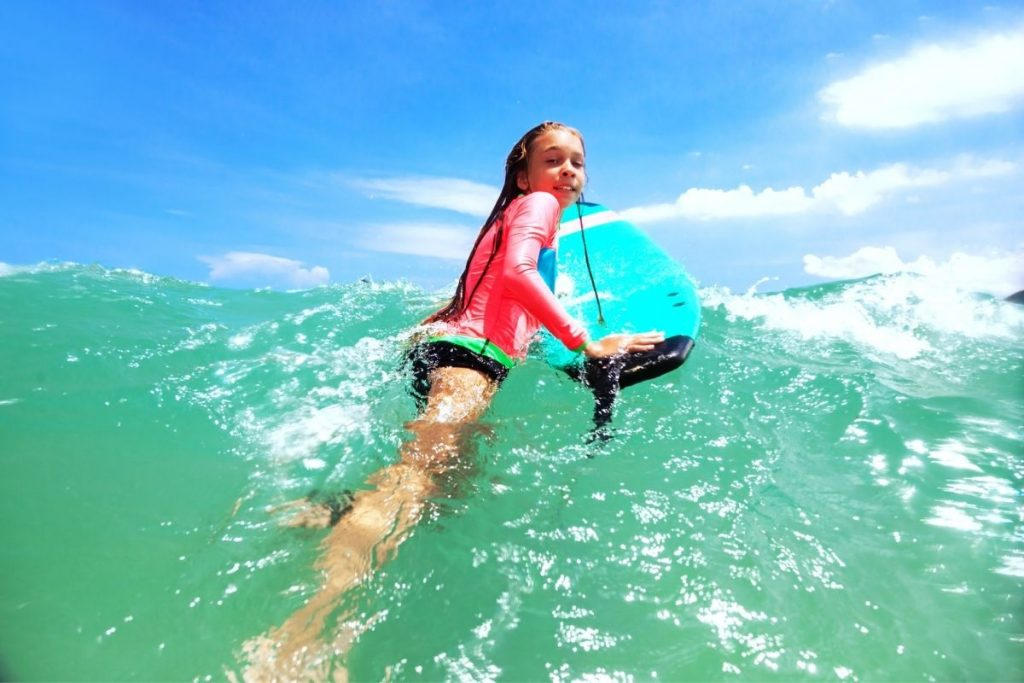 preteen with her surfboard