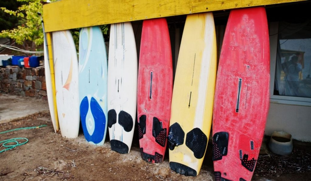six old surfboards standing under a shed
