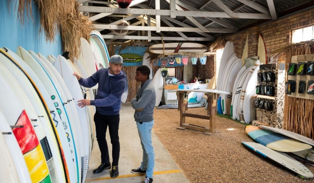 surf shop owner helping a customer to buy a surf board