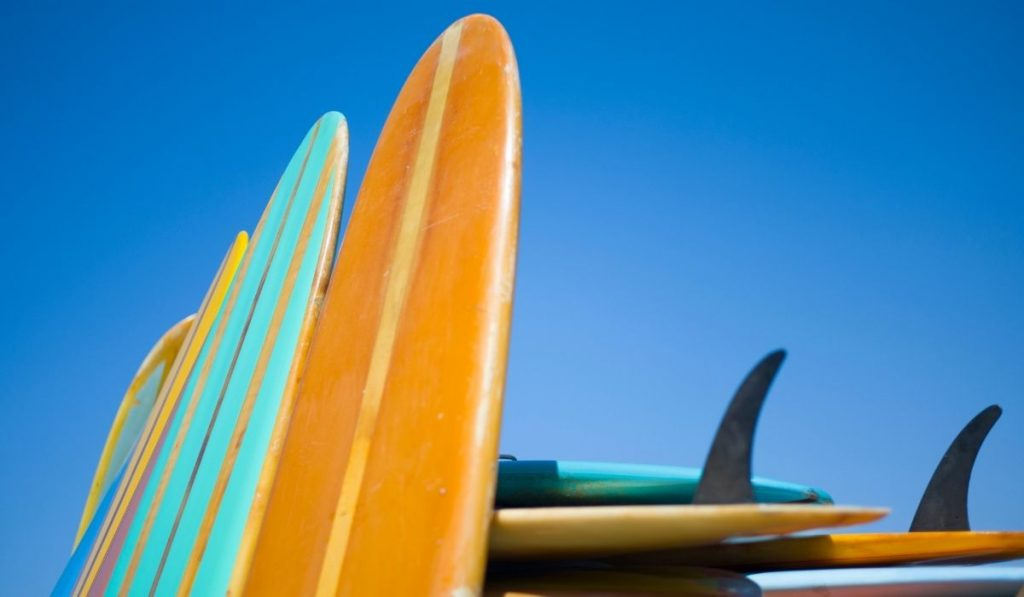 surfboards leaning on a stack of surfboards