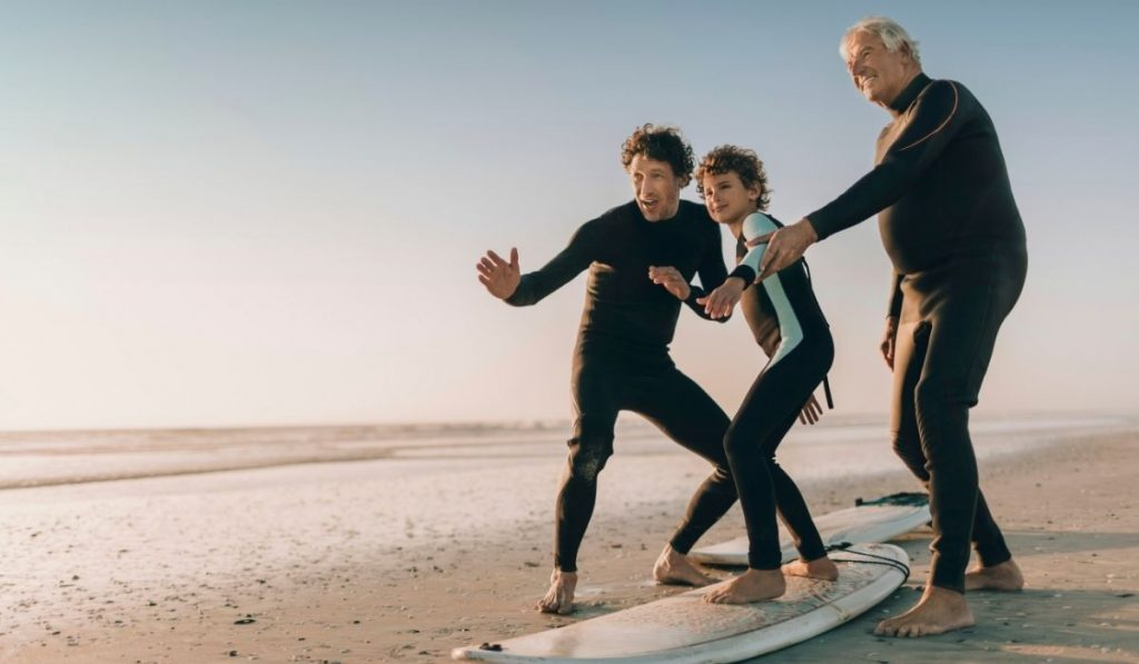 two adult men teaching a kid the proper surfing position