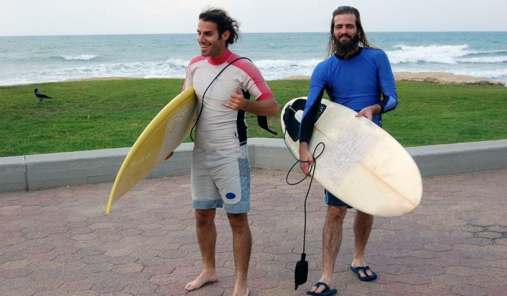 two men holding their surfboards at the beach