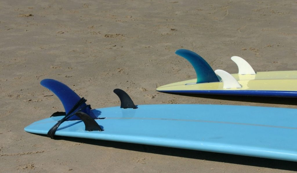 two surfboards with three fins
