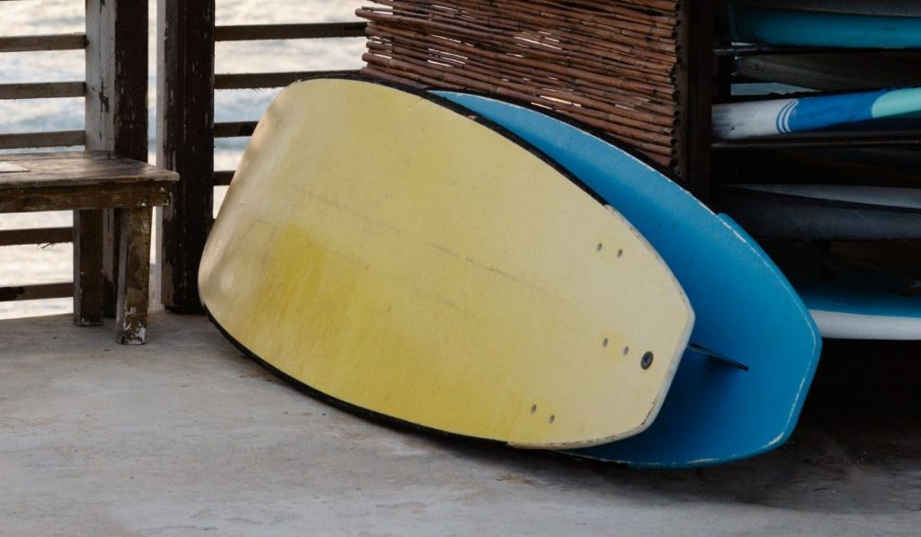 yellow and blue surfboard leaning on a bamboo surfboard rack