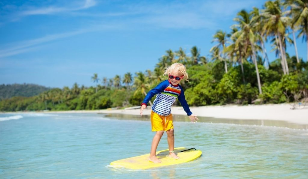 young girl on a yellow surf board with coconut trees in the background