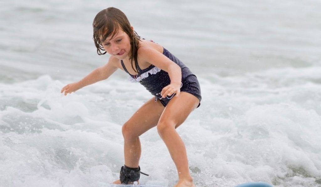 young girl with polka dot bathing suit surfing