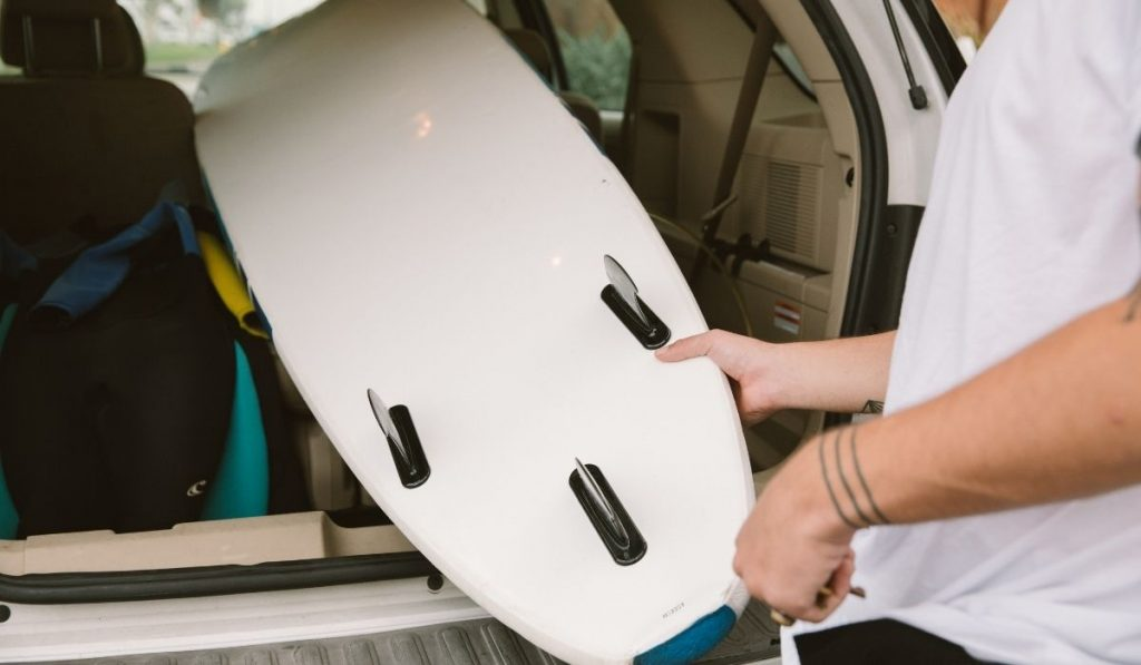 man leaving his surfboard inside his car
