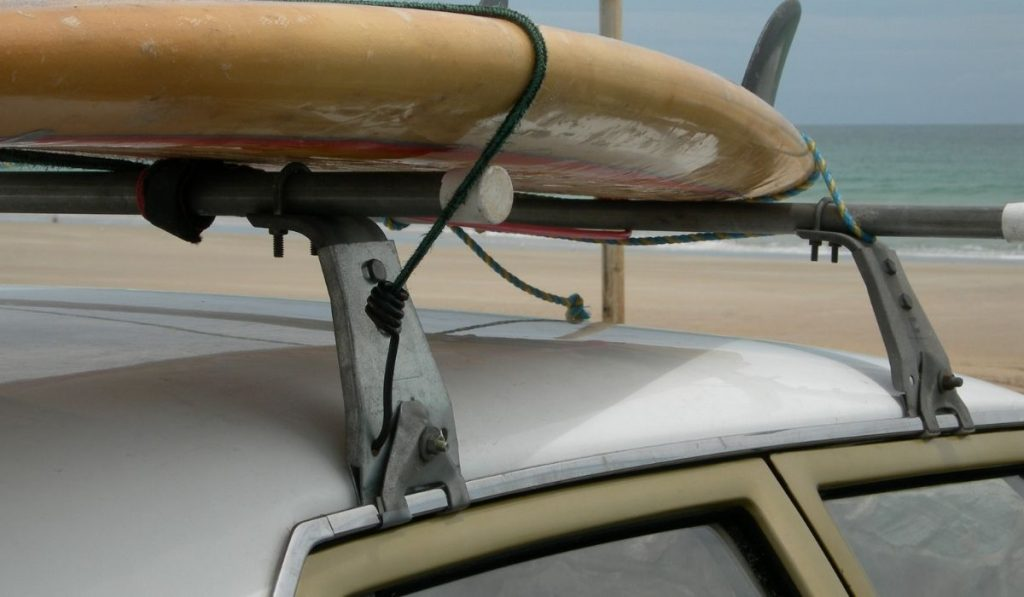 old surfboard strapped in a car on the beach