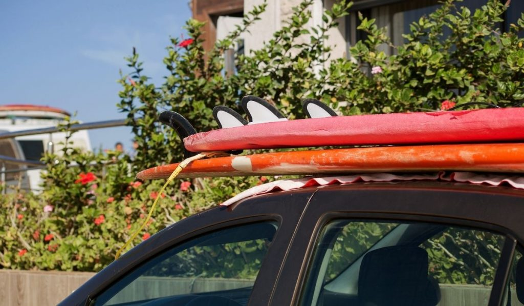 red and orange surfboards on top of the car without straps