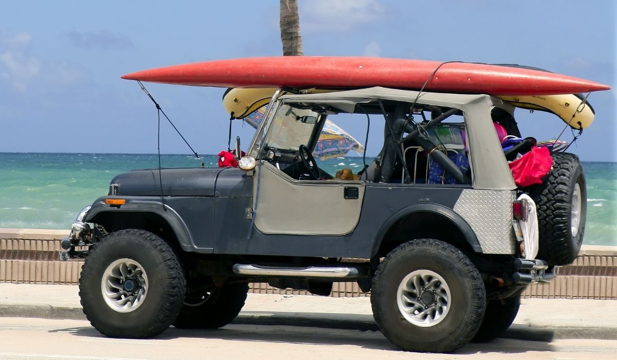 red surfing board on top of a jeep